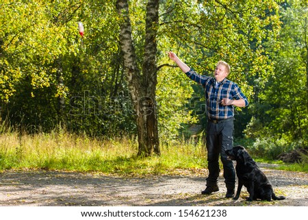 Dog owner trains his labrador retriever on outdoor, dog sits on alongside, horizon format