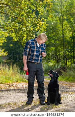 Dog owner trains his labrador retriever on outdoor, dog sits on alongside, vertical format