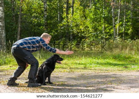 Dog owner trains his labrador retriever on outdoor, horizon format