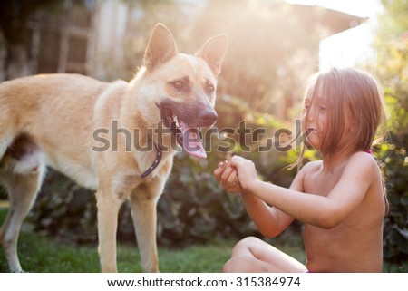 Dog playing with child on the yard