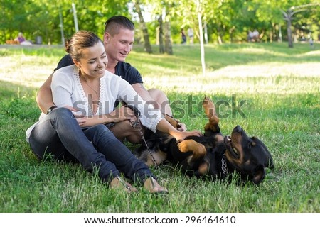 Dog plays with the owners on the grass. Focus on couple - stock photo