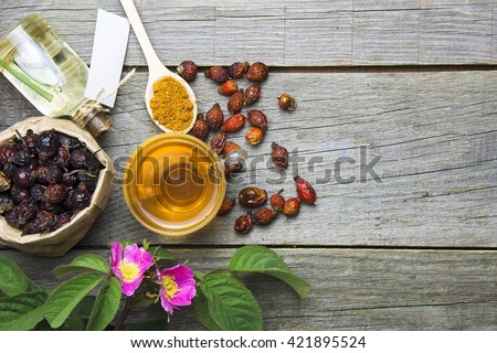 Dog rose, bunch branch Rosehips. Different types Rosa canina hips and hawthorn. rose hip flowers and bottles of essential oil. Herbal tea.  room for text. selective focus, toned image - stock photo