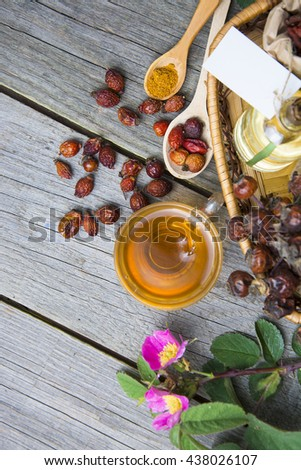Dog rose, bunch branch Rosehips. Different types Rosa canina hips and hawthorn. rose hip flowers and bottles of essential oil. Herbal tea. room for text. selective focus, toned image