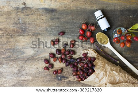 Dog roses and essential oil, bunch of dog rose. Different types Rosa canina hips and hawthorn, dry goji berries, briar powder in wooden spoon. chinese herbal medicine selection in wooden  - stock photo