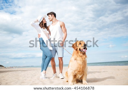 Dog sitting in front of happy young couple standing and hugging on the beach - stock photo