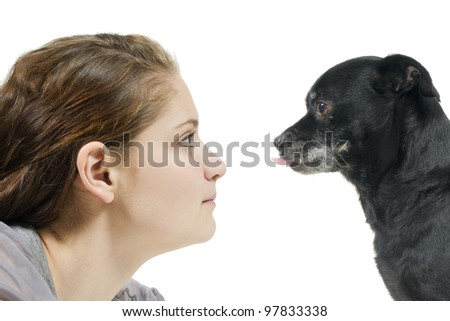 Dog sticking tongue out at girl during staring contest - stock photo