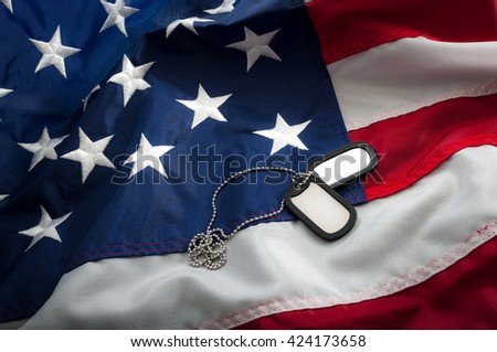 Dog tags are used for the identification of dead and wounded soldiers; they have personal info about the soldier and convey basic medical info, like blood type and history of inoculations on USA flag - stock photo