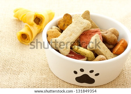 Dog treats in white bowl on burlap cloth - stock photo