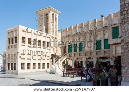 DOHA, QATAR - MARCH 8, 2015: Porters await work outside part of the imposing Souq Waqif tourist attraction