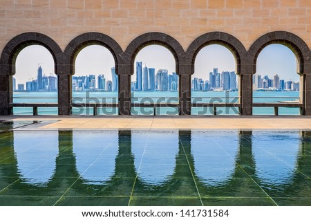 Doha skyline through the arches of the Museum of Islamic art, Doha, Qatar - stock photo