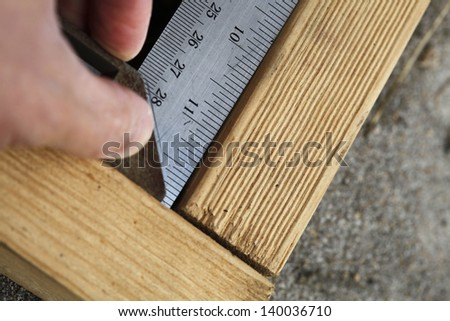 Doing calculations to ensure right angle on the wooden beam. - stock photo