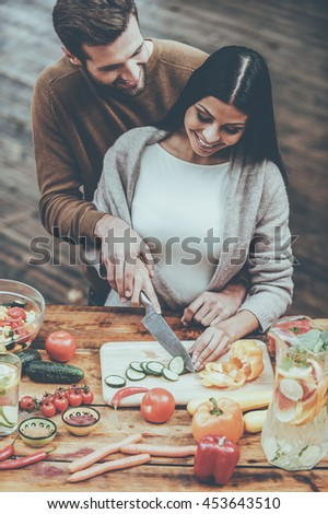 Doing everything together. Top view of beautiful young couple preparing food together and smiling - stock photo