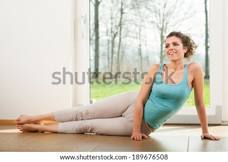 Doing exercises in front of the window of her house - stock photo