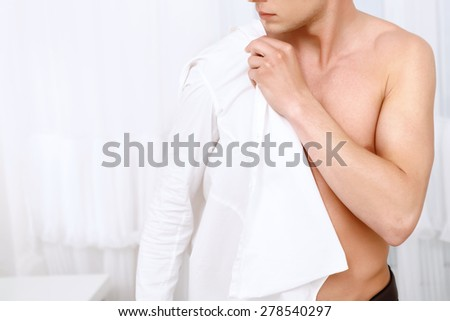 Doing gently. Close up of handsome muscleman putting on white shirt on background of white decorated room.