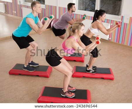 Doing squats with dumbbells on the steps - stock photo