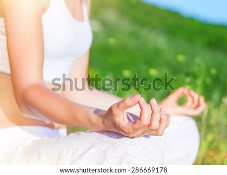 Doing yoga outdoors, woman sitting in the park in lotus pose and meditate, body part, soft focus, healthy lifestyle, finding harmony and soul balance