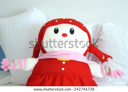 Doll and pillows on bed / A girl doll - stock photo
