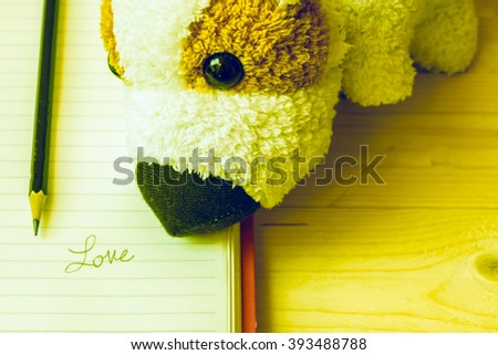 Doll dog and written love on notebook with pencil,wooden background,concept vintage - stock photo