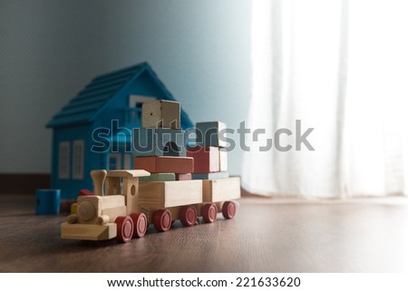 Doll house and wooden toy train on hardwood floor next to a window. - stock photo