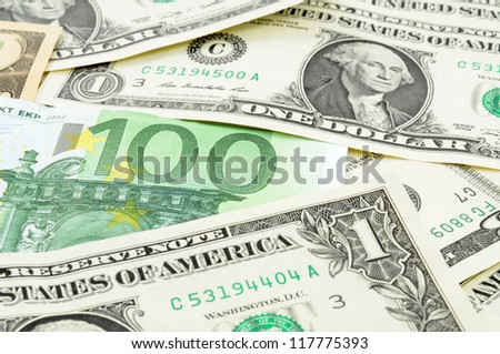 Dollar and a 100 Euro bill in a studio shot with selective focus