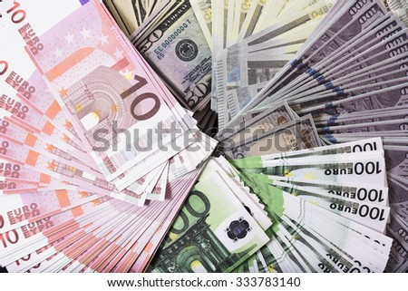 Dollar and euro banknotes on the table. - stock photo