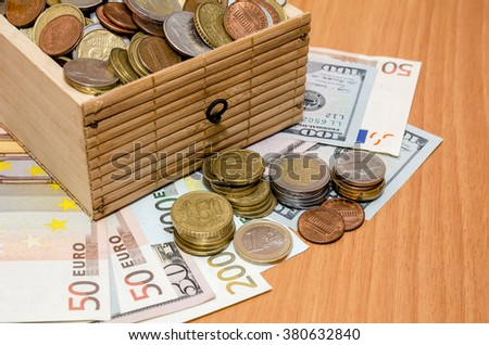 Dollar and euro money with coins in the treasure chest - stock photo