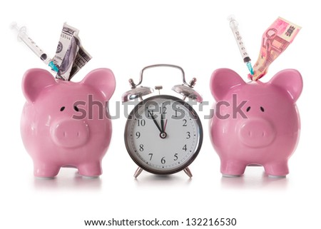 Dollar and euro notes and syringes sticking out of piggy banks with alarm clock on white background - stock photo