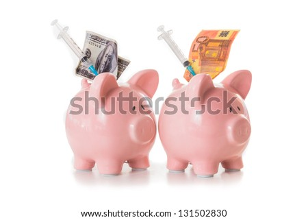 Dollar and euro notes and syringes sticking out of pink piggy banks on white background - stock photo