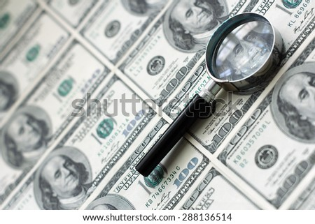Dollar background with magnifying glass and copy space on left - stock photo