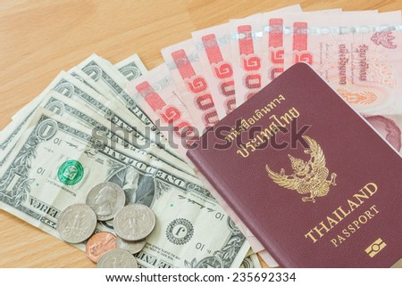 dollar baht bills and coins thai passport - stock photo