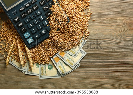 Dollar banknotes, calculator and wheat grains on wooden background. Agricultural income concept