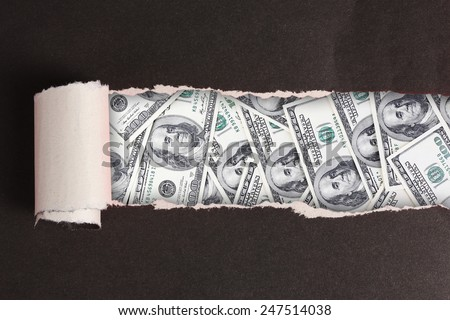 Dollar banknotes through torn black paper - stock photo