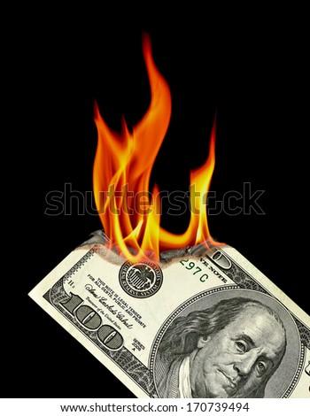 Dollar bill burning on black background - stock photo