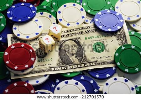 Dollar bill casino chips and dice hidden under  question mark- risk concept - stock photo