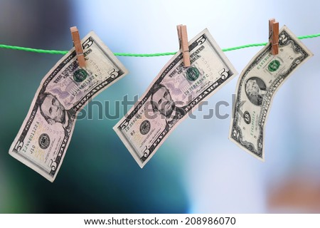 Dollar bills hanging on rope attached with clothes pins. Money-laundering concept. On bright background. - stock photo