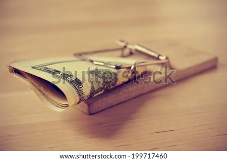 dollar bills in a mousetrap on a table with a retro effect - stock photo