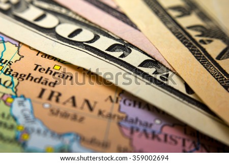 Dollar bills on top of a map of Iran - stock photo