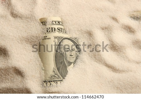 dollar bills partially buried in sand. Conceptual image depicting a safer alternative to investing. Macro with shallow dof. - stock photo