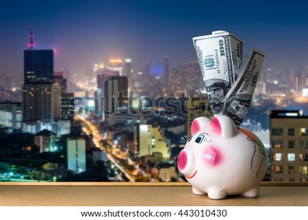 Dollar cash money and piggy bank on table with blur city night background. business, finance, investment, saving concept - stock photo