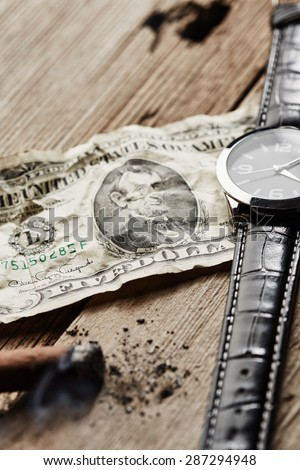 Dollar, clock and cigar on wooden background