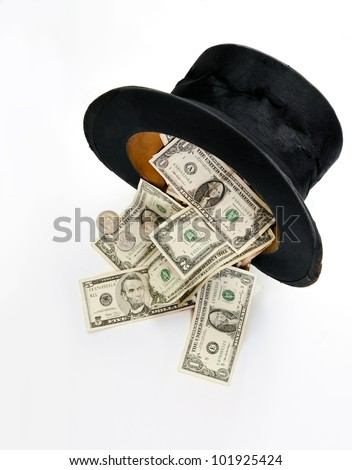 Dollar currency bills and coins overflowing out an old well-worn black top hat isolated on white background. - stock photo
