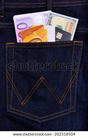 Dollar, euro bank notes and credit cards in jeans pocket