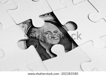Dollar hidden under  Puzzle, business concept of Solution- close up - stock photo