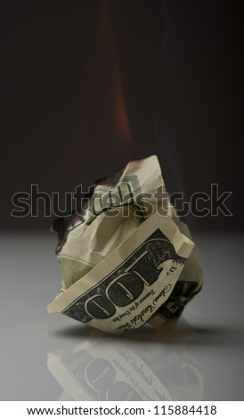 dollar note burning in fire on black background - stock photo