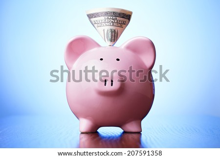 Dollar note in a piggy bank sticking out pf the slot on its back as it faces the camera on a blue background conceptual of savings, finances and investment