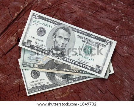 Dollar notes against wooden background - stock photo