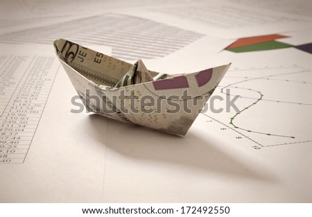 Dollar paper boat on data  - stock photo