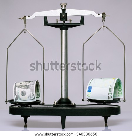 Dollar's and euro's banknotes on the scale, neutral background - stock photo