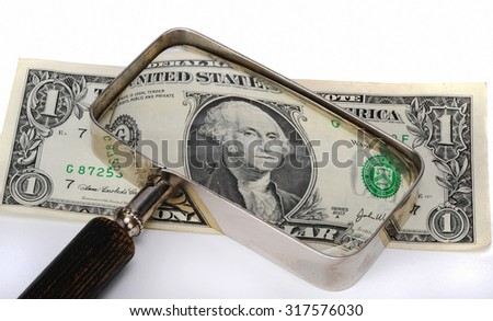 Dollar under investigation using magnifier.