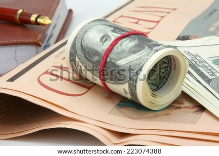Dollars, an organizer and a pen on a newspaper, isolated on white - stock photo